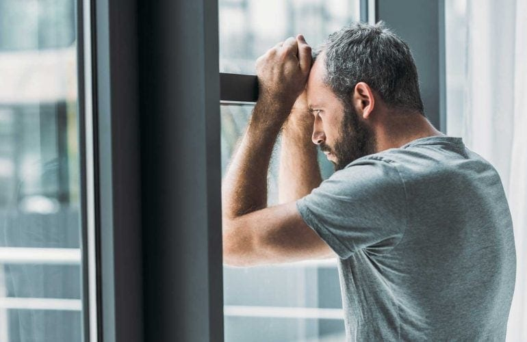 A man suffering from depression, looking forlorn out his window.